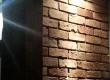 Podświetlona ścianka z cegły przy wejściu do domku
