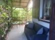 Zadaszony i zacieniony, komfortowy taras z kanapą i meblami ogrodowymi
