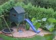 Plac zabaw - piaskownica, trampolina, drewniany domek w ogrodzie